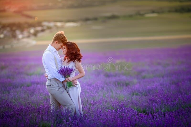 Nieuw huwelijkspaar die zich op lilac gebied en de omhelzingen van lavendelbloemen bevinden Na huwelijksceremonie De bruid is bin royalty-vrije stock fotografie