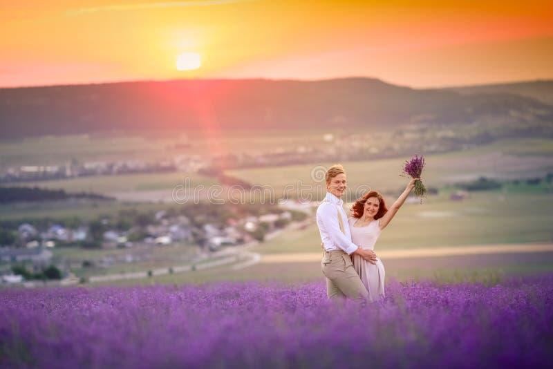 Nieuw huwelijkspaar die zich op lilac gebied en de omhelzingen van lavendelbloemen bevinden Na huwelijksceremonie De bruid is bin royalty-vrije stock foto