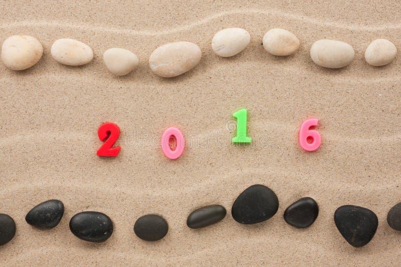 Nieuw jaar 2016 geschreven op het zand onder stenen stock afbeeldingen