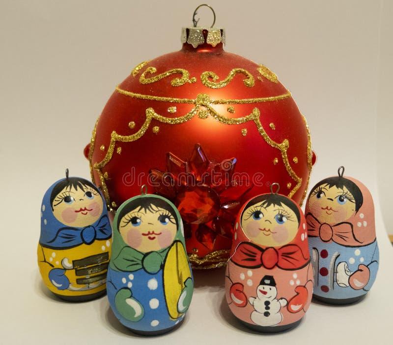 Nieuw jaars speelgoed, kleine Russische poppen, rode glasbal stock afbeeldingen