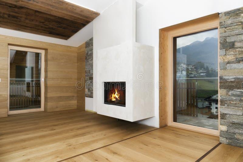 Nieuw leeg woonkamerbinnenland met open haard en hardhoutvloer stock afbeeldingen