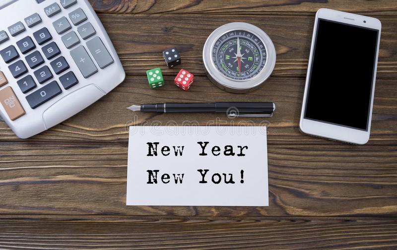 Nieuw nieuwjaar dobbelt u geschreven op document, houten bureau als achtergrond met calculator, omringt, slimme telefoon en pen stock afbeelding