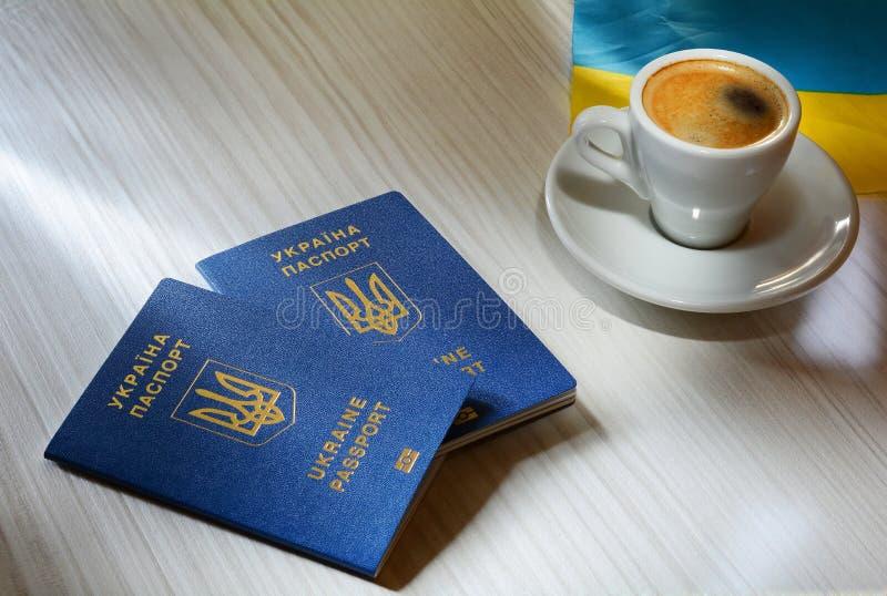 Nieuw Oekraïens blauw biometrisch paspoort met identificatiespaander op houten achtergrond Een kop van koffie en een paspoort stock foto