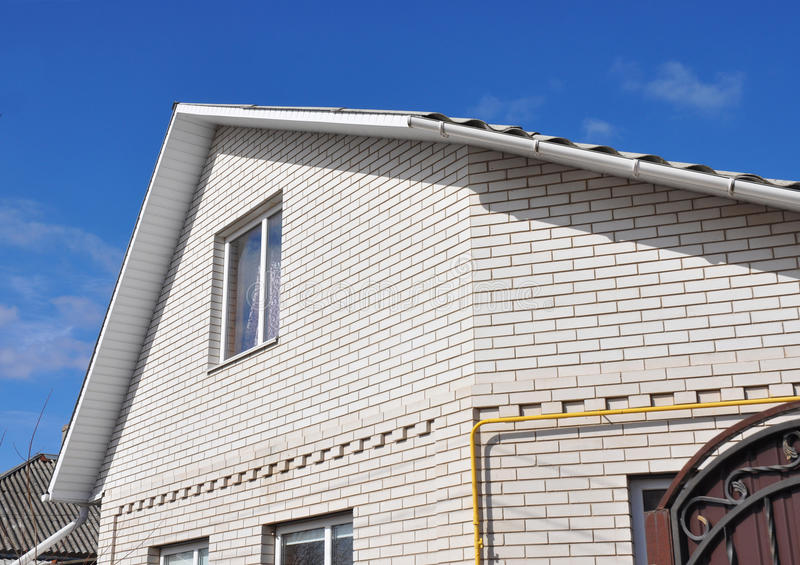 Nieuw wit baksteenhuis met close-up van probleemgebieden voor dakgoot het waterdicht maken royalty-vrije stock foto's