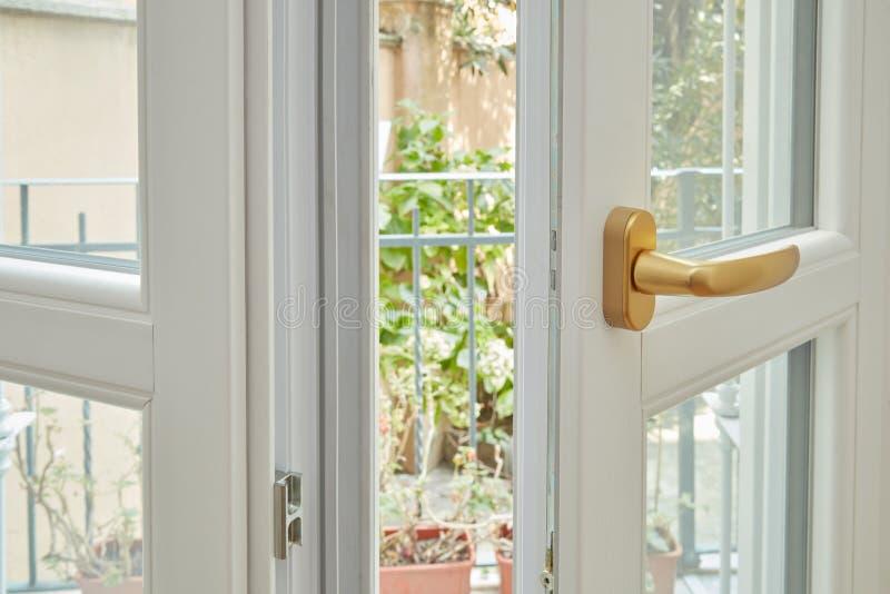 Nieuw, wit dubbel verglaasd venster met gouden handvat stock afbeeldingen