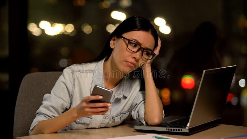 Nieuważny młodej kobiety gawędzenia smartphone, wystrzeganie praca, akcydensowa nieistotność zdjęcie stock