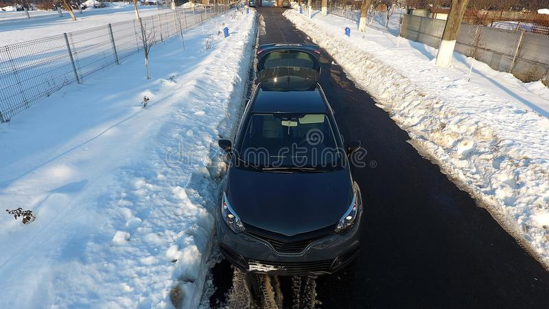Nieuwe auto in de sneeuw, hommelmening stock foto