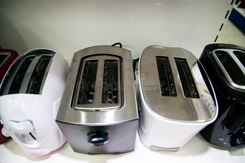 Nieuwe broodroosters op de plank in de opslag Assortiment van een keuken modieuze moderne mooie modieuze toestellen bij huishoude stock foto's