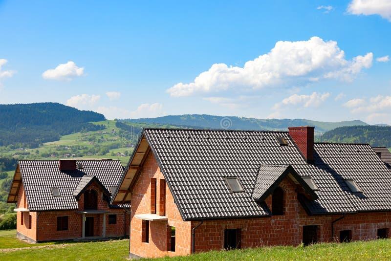 Nieuwe die huizen op groene heuvels worden gecreeerd Landelijk landschap royalty-vrije stock foto's