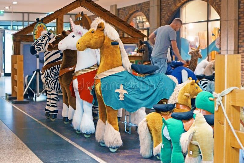 Nieuwe Duitse tendens voor kinderen, zogenaamde 'Gealigneerde Dieren in winkelcomplex, moderne hobbelpaarddieren die zich rond ku royalty-vrije stock foto's