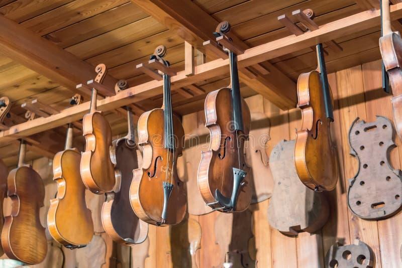 Nieuwe en oude violen in workshop stock foto's
