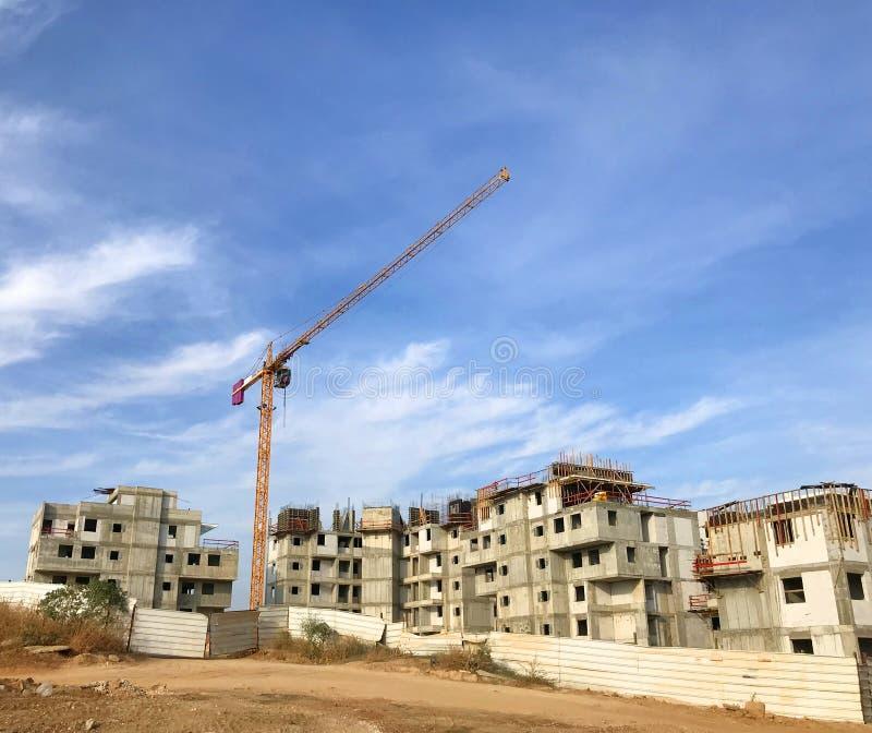Nieuwe flatsbouwwerf Kraan over blauwe hemel, bouwstenen, bezits helft-klaar huizen, het concept van de ontwikkelingsindustrie royalty-vrije stock afbeelding