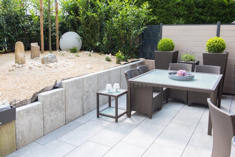 Nieuwe geschikte steentuin met terras en Lijst en stoelen stock afbeeldingen