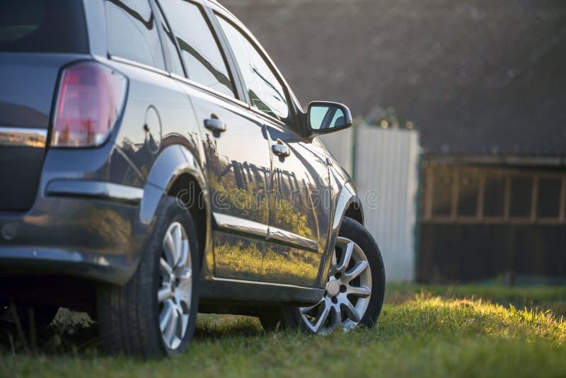 Nieuwe glanzende grijze die auto op groen gras op vage zonnige de zomer landelijke achtergrond wordt geparkeerd royalty-vrije stock foto's