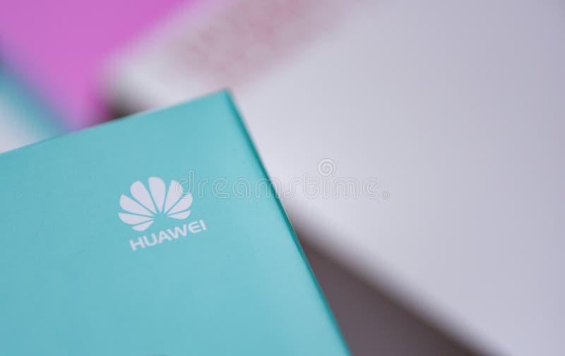 Nieuwe huaweismartphone van de pakketdoos met wit HUAWEI-embleem op hoogste blauwe achtergrond stock fotografie