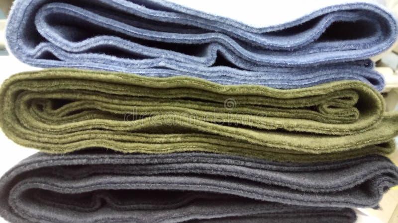 Nieuwe industriële groene, zwarte en blauwe broodjesachtergrond Concept: materiaal, stof, vervaardiging, kledingstukfabriek, nieu stock foto