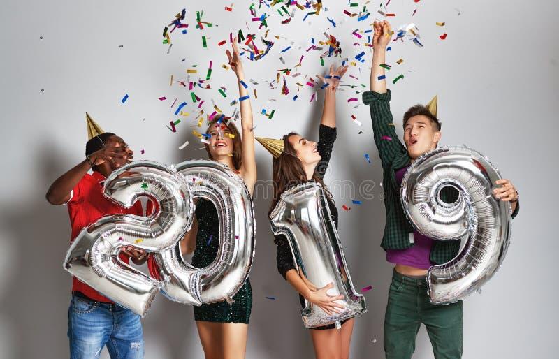 Nieuwe jaarpartij bedrijf van vrolijke vrienden met ballonssnummer 2019 royalty-vrije stock foto's
