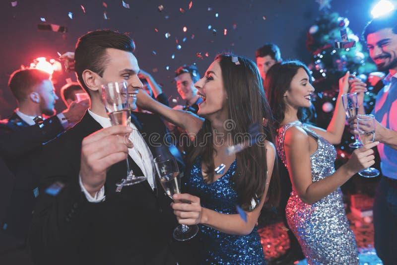 Nieuwe jaarpartij Jong paar die met glazen champagne in handen dansen stock afbeeldingen