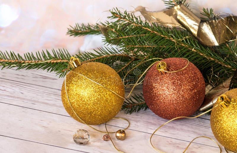 Nieuwe jaaruitnodiging Gouden ballen en nieuwe slinger met Kerstboomtakken stock foto