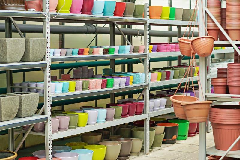 Nieuwe kleurrijke ceramische en plastic bloempotten op de planken stock afbeelding