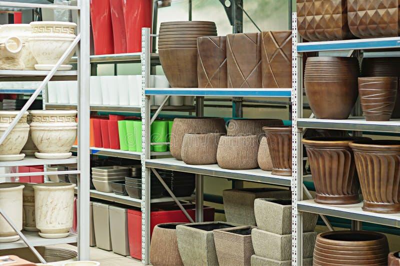 Nieuwe kleurrijke ceramische en plastic bloempotten op de planken stock fotografie