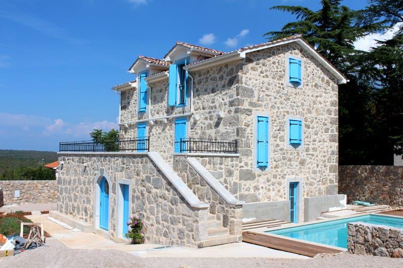 Nieuwe Mediterrane die villa met steen in in traditionele stijl met blauwe houten vensterzonneblinden en deuren naast zwembad wor stock foto
