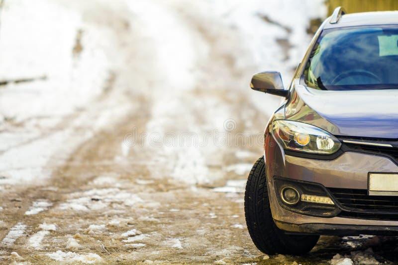 Nieuwe moderne grijze die auto op een straat in de winter wordt geparkeerd stock foto's