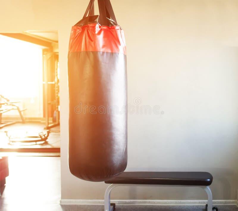 Nieuwe moderne ponsenzak in de zaal voor sporten en vechtsporten op de achtergrond van het venster waarin de zonsondergang, exemp stock afbeelding
