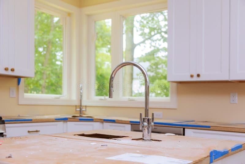 Nieuwe moderne witte keuken met de gebouwde kraan van het chroomwater stock foto