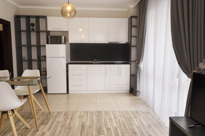 Nieuwe moderne woonkamer met keuken Nieuw huis Binnenlandse fotografie Houten Vloer stock afbeelding