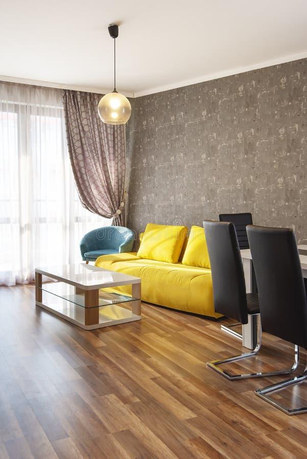 Nieuwe Moderne Woonkamer Nieuw huis Binnenlandse fotografie Houten Vloer Eettafel met reeks stoelen, gele bank stock fotografie