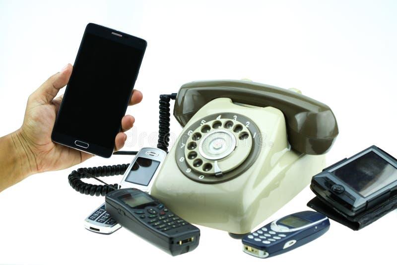 Nieuwe slimme telefoon met oude telefoon op witte achtergrond Nieuwe communicatietechnologie royalty-vrije stock afbeeldingen