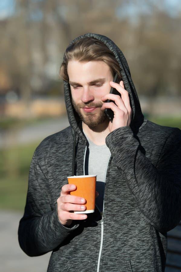 Nieuwe technologie en het moderne leven Kerel met smartphone en meeneemdrank op verse lucht Gebaarde mens in beschikbaar de koffi stock foto's