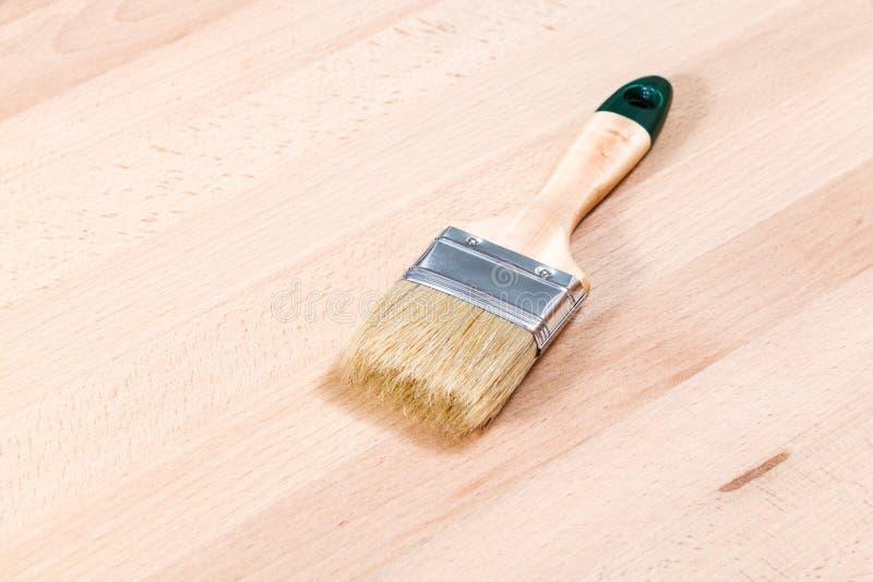 Nieuwe verfborstel op beuk houten raad stock foto's