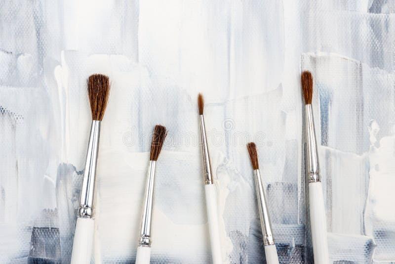 Nieuwe verfborstels op zwart-wit canvas royalty-vrije stock foto