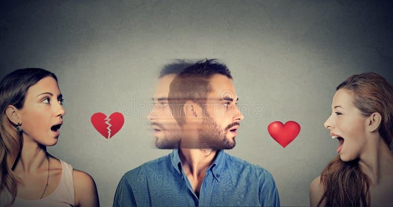 Nieuwe verhouding Portret van twee vrouwen en mannen één die elegante kleren op zwarte dragen Man dalingen van liefde met een and royalty-vrije stock foto's
