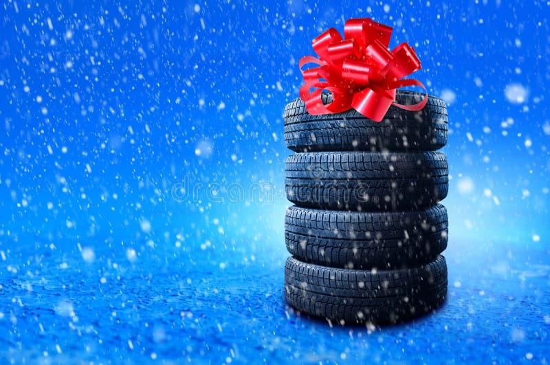 Nieuwe winterbanden als cadeau De banden stapelen met een grote rode boog, als heden of een bonus voor het kopen van een auto Ban royalty-vrije stock foto
