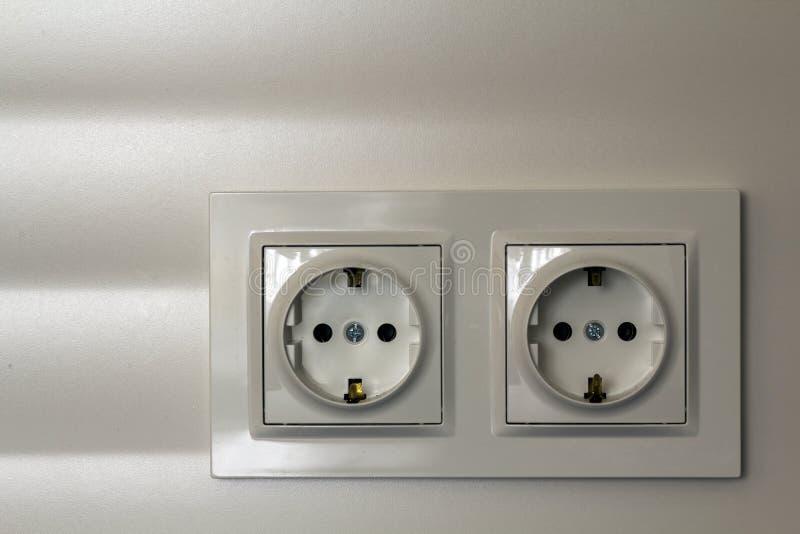 Nieuwe witte glanzende plastic elektrische dubbele contactdozen op witte muurachtergrond Voordelen en comfort van moderne huizen royalty-vrije stock afbeeldingen