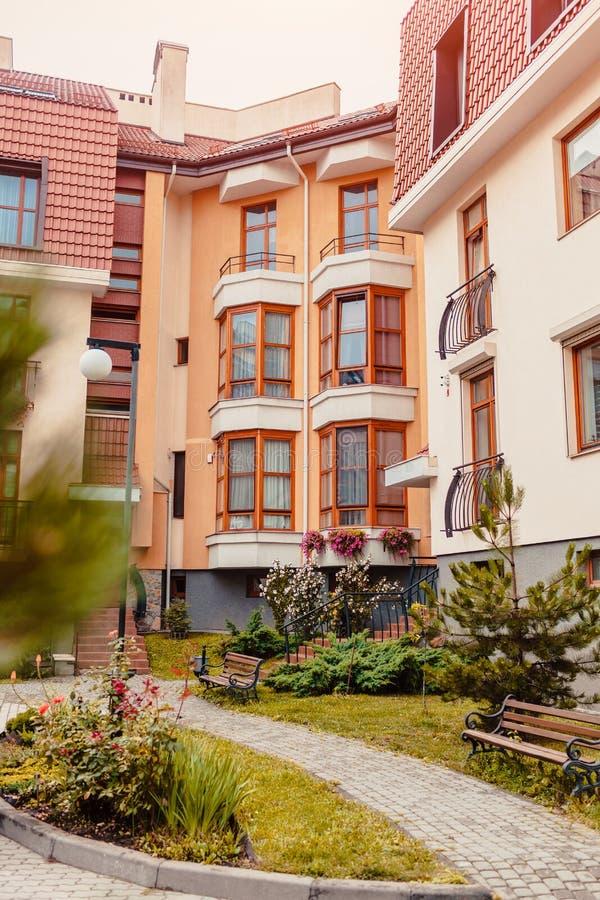 Nieuwe woningbouw met meerdere verdiepingen Modern die huis in rode en oranje kleuren wordt geverft royalty-vrije stock afbeeldingen