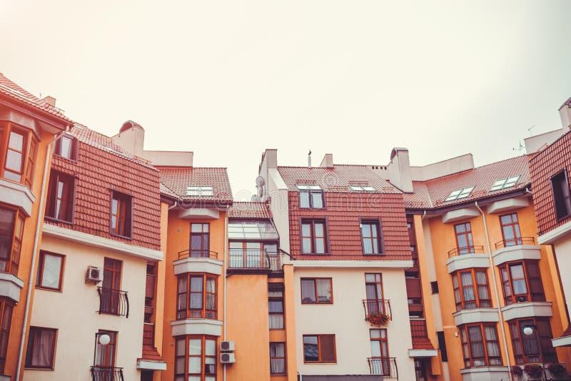 Nieuwe woningbouw met meerdere verdiepingen Modern die huis in rode en oranje kleuren wordt geverft royalty-vrije stock afbeelding