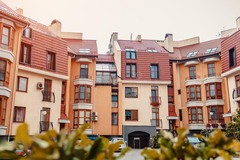 Nieuwe woningbouw met meerdere verdiepingen Modern die huis in rode en oranje kleuren wordt geverft stock afbeelding