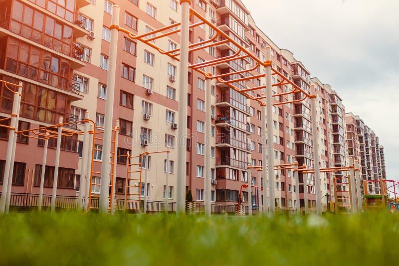 Nieuwe woningbouw met meerdere verdiepingen Sportengrond met gazon voor het huis stock foto