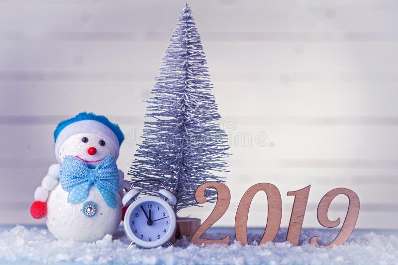 Nieuwe Year' s samenstelling: klok, sneeuwman, inschrijving 2019 en Kerstboom op een houten achtergrond royalty-vrije stock foto