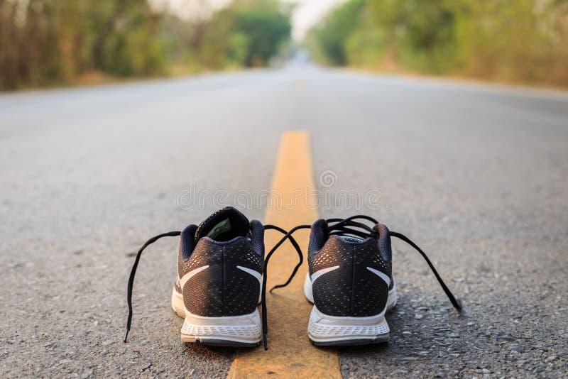 Nieuwe zwarte loopschoenen op asfaltweg in ochtendtijd stock afbeeldingen