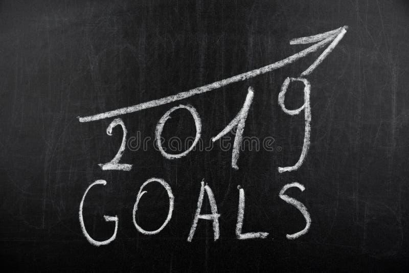 Nieuwjaar 2019 doelstellingen met een het toenemen krijt van de pijltekst op een bord Bord met tekst 2019 Doelstellingen wordt ge stock afbeelding