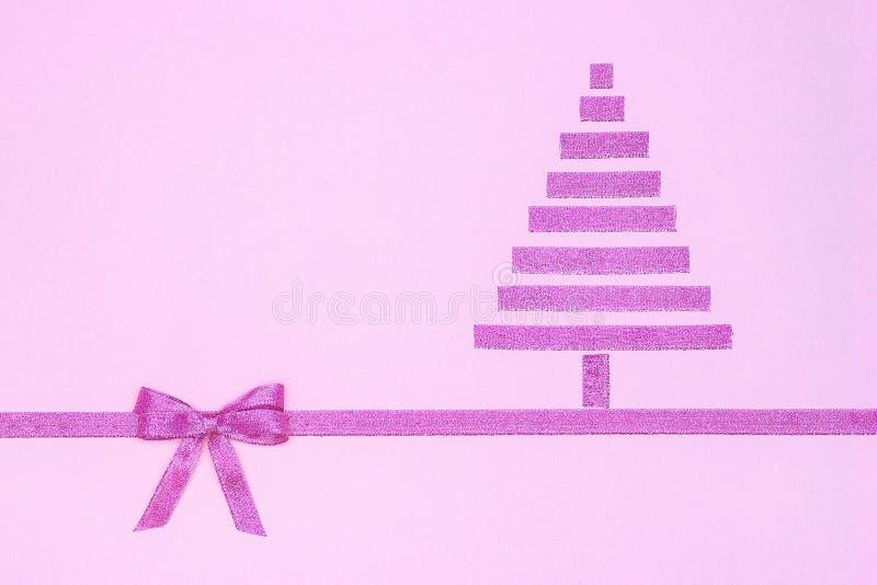 Nieuwjaar en de samenstelling van Kerstmis Abstracte purpere Kerstmisboom van decoratief glanzend lint met boog op roze royalty-vrije stock afbeelding