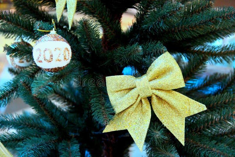 Nieuwjaar: gouden boog en gouden bal met witte tussenvoegsel en inscriptie 2020 tegen de achtergrond van bijkantoren van royalty-vrije stock fotografie