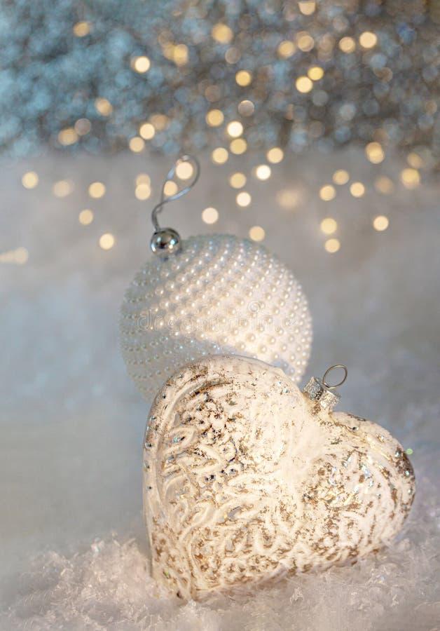 Nieuwjaar of Kerstmisdecoratie Glas wit hart en een bal met parels op een sneeuw Vage achtergrond van het schitteren bokeh stock foto