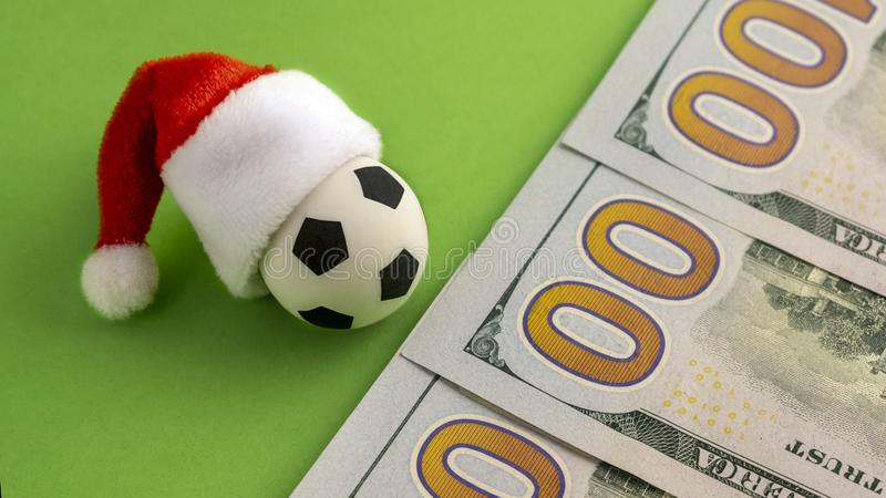 Nieuwjaar of Kerstmisverrassing Een voetbalbal met een Santa Claus-hoed naast de honderd dollarsrekeningen Nul op green royalty-vrije stock fotografie