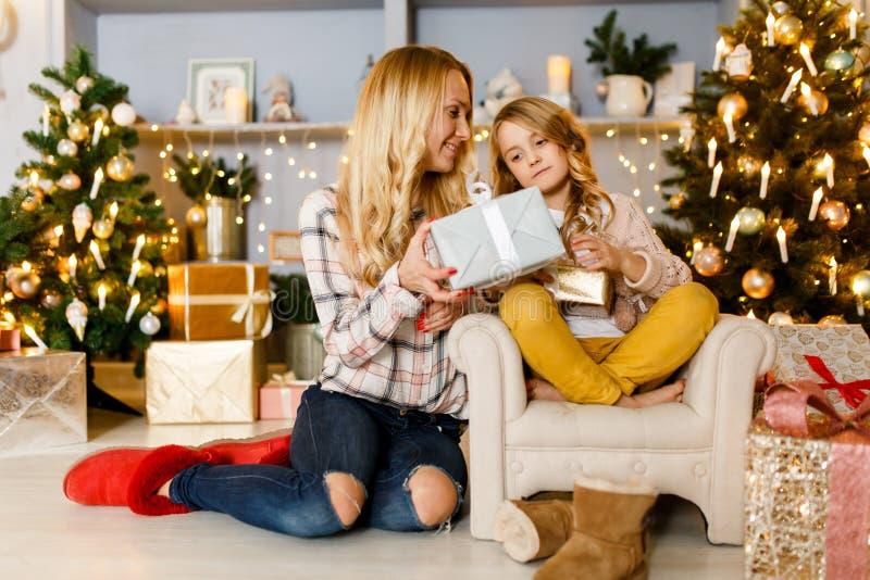 Nieuwjaar` s beeld die van moeder gift geven aan dochterzitting op stoel royalty-vrije stock afbeeldingen